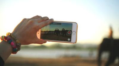 Frau hält Smartphone, um Social Video aufzunehmen